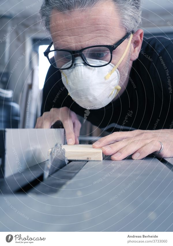Man with a dust mask and goggles working on a circular saw tools machinery handyman worker manufacture activity protective protection occupational safety