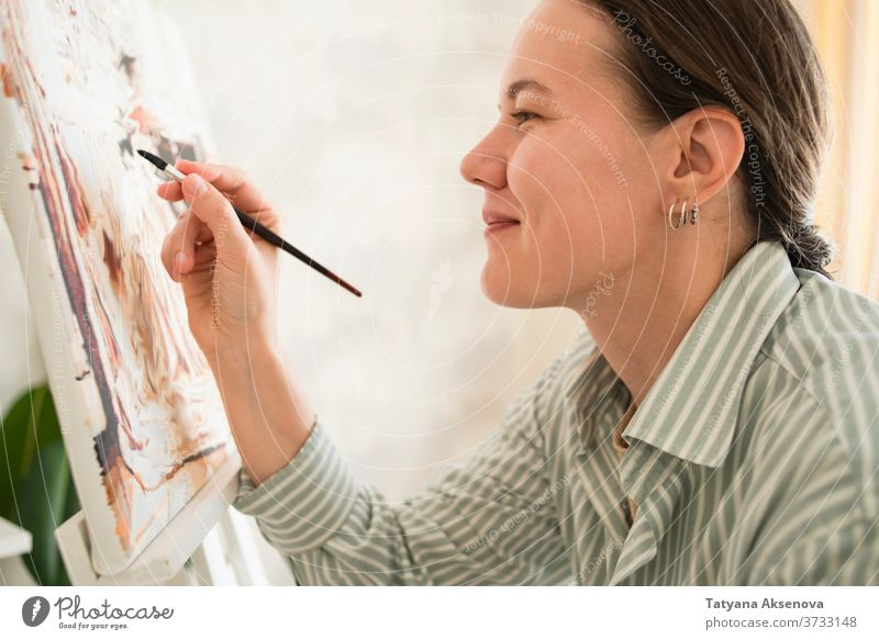 Woman in shirt drawing picture at easel at home artist paint female artistic artwork painter adult occupation education palette canvas person brush paintbrush