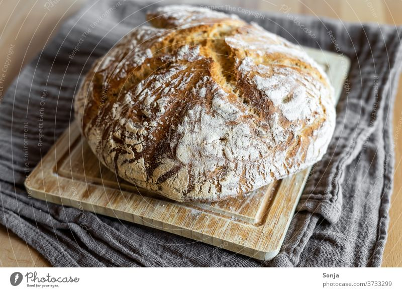 Freshly baked loaf of bread with crust on a wooden cutting board Crisp Crust tea towel Food Rustic Bakery Bread Breakfast Healthy Eating traditional Baking