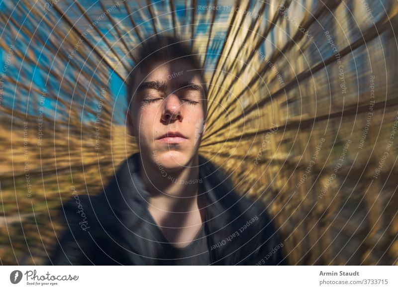 portrait of a dreaming young man with moving background meditation concentration imagination inspiration serious beautiful handsome dynamic speed motion blur