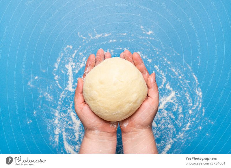 Bread dough hold in hand over a blue table. Uncooked dough. Baking at home background bake bakery baking bread bread dough buns concept cooking copy space