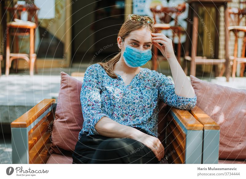 Young woman with mask outdoors in coffee shop thinking 2020 adult beautiful caffè caucasian city concept coronavirus covid-19 every day life