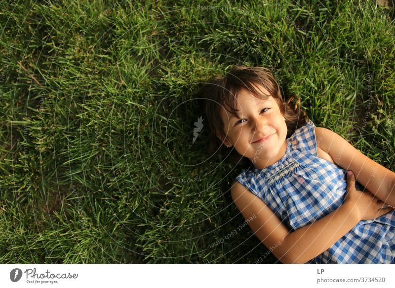 girl smiling at the camera lying on the grass Grass Upper body Portrait photograph Copy Space left Structures and shapes Pattern Abstract Exterior shot