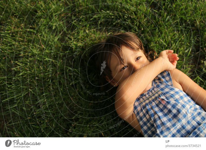 little girl laying on the grass, looking at the sky Upper body Portrait photograph Pattern Structures and shapes Abstract Exterior shot Subdued colour