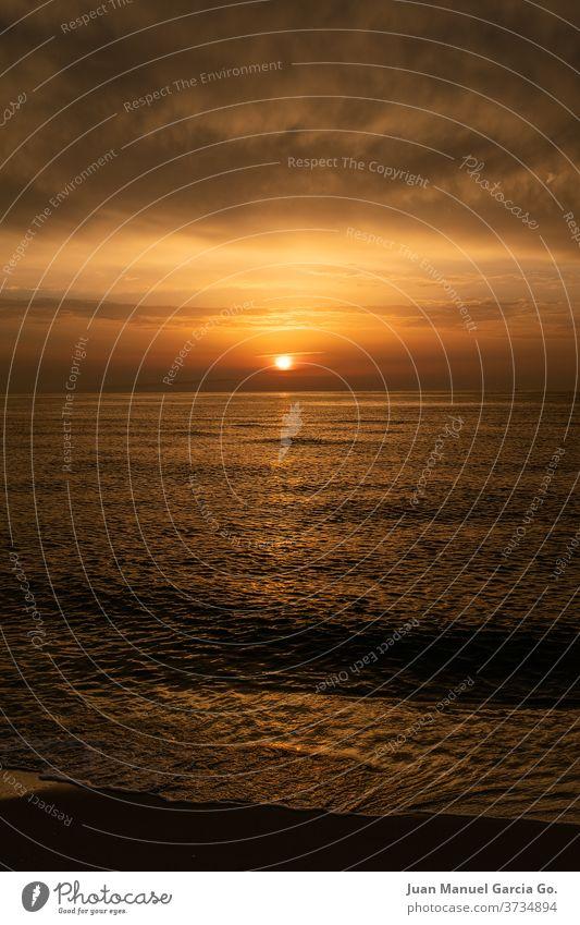 A stunning view of a sea during orange sunset water sky nature ocean beach cloud light coast sunlight horizon wave dawn travel clouds landscape sand shore
