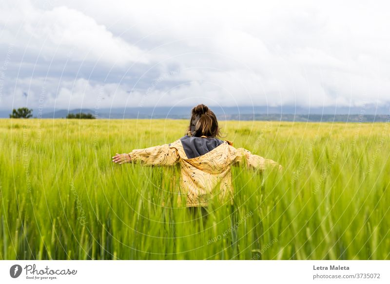 Kid running in the countryside when storm is coming land field spring green lawn plants garden kid yellow pullover freedom free kid nature clouds weather rural