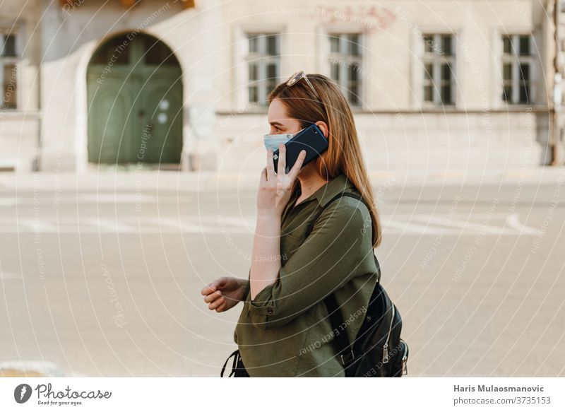 Woman with face mask talking on the phone outside, profile view 2020 adult beautiful blue caffè caucasian child childhood city concept coronavirus covid-19