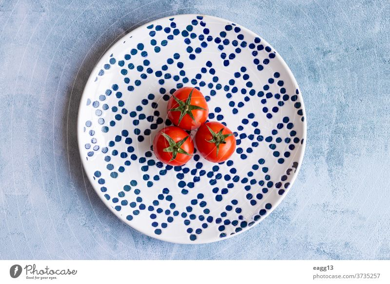 Cherry tomatoes on blue dotted plate abundance alimentation backgrounds cherry chic close-up colors colourful colours composition diversity eco ecology farming