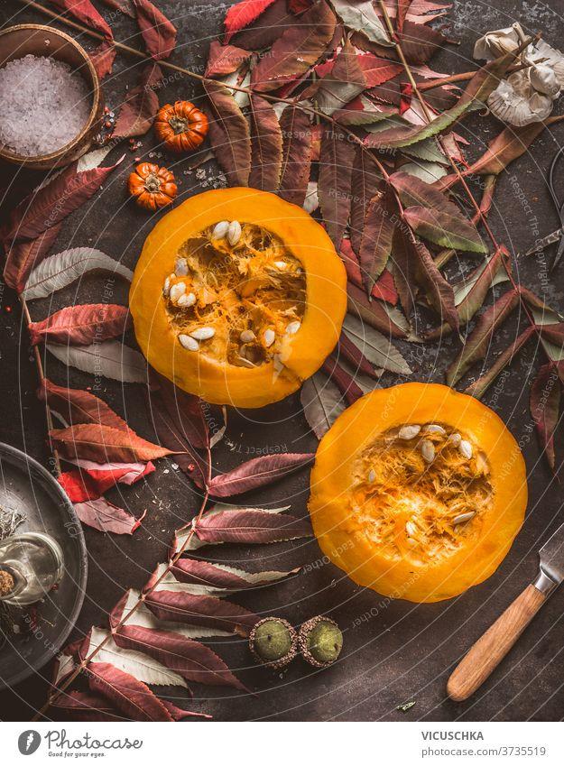 Seasonal food. Half Hokkaido pumpkin with seeds, knife and fall leaves on dark kitchen table. Autumn mood. Top view seasonal food sliced hokkaido autumn mood