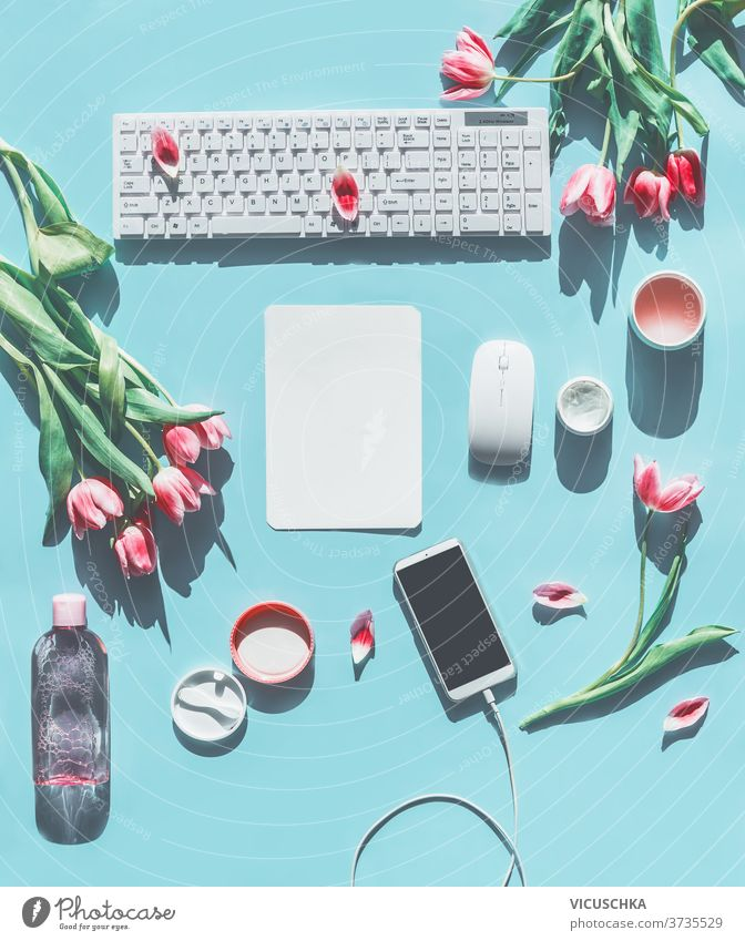 Spring concept . Smartphone mock up. PC keyboard, tulips and natural cosmetic products. Light blue background. Lifestyle beauty blogging concept. Flat lay. Top view
