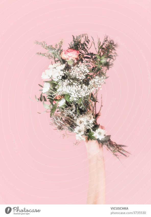 Women hand holding bouquet of fresh flowers. Light pink background. Romantic concept. Front view . Pastel color pastel color light romantic spring concept
