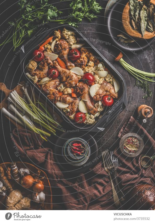 Fresh cooked food in baking dish with various ingredients. Kitchen equipment. Dark concrete background.Flat lay. Top view copy space kitchen cloth fresh forks