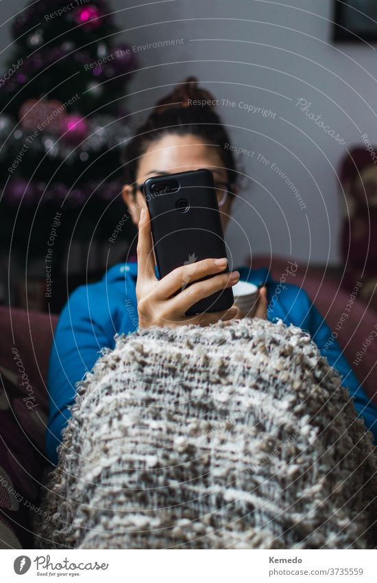 Woman sitting on a sofa with a coffee cup using a smartphone on a cold morning of Christmas. Background with decorated christmas tree. mobile woman cell blanket