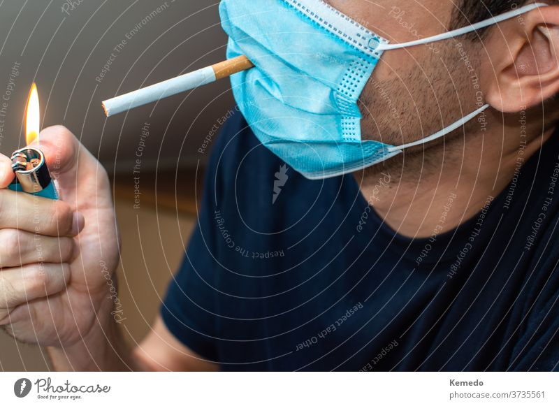 Young man with mask lighting a cigarette. Coronavirus funny concept coronavirus covid crazy strange rare new normal idiot stupid person silly joke young party