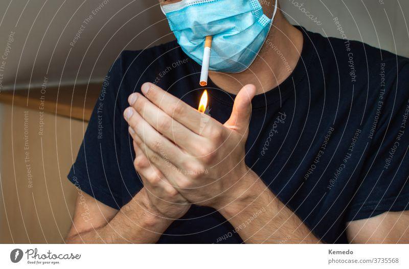 Man lighting a cigarette while wearing face mask. Covid funny concept coronavirus covid 19 man person smoke leisure home party drug addiction strange rare fail
