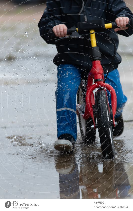 Child on a running bike rides through the puddle with a swing impeller Children's game Toddler Puddle puddle picture Inject Drops of water Wet Water Playing