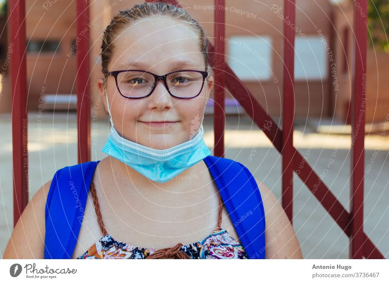 Portrait of a blonde chubby girl with glasses, a blue backpack and a face mask. Back to school. schoolgirl coronavirus protection protective teenager female