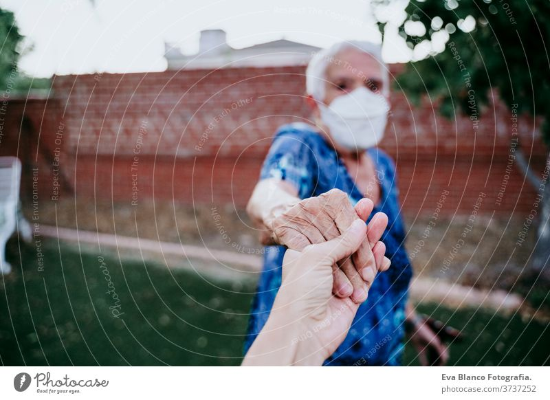 old woman wearing protective mask holding hands with unrecognizable woman. New normal concept lady young two generations follow me old lady corona virus elder