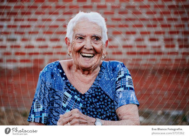 portrait of old lady in her 80s laughing happily happy smiling joy woman elderly home white hair grey hair mental grandmother aged health care looking emotion