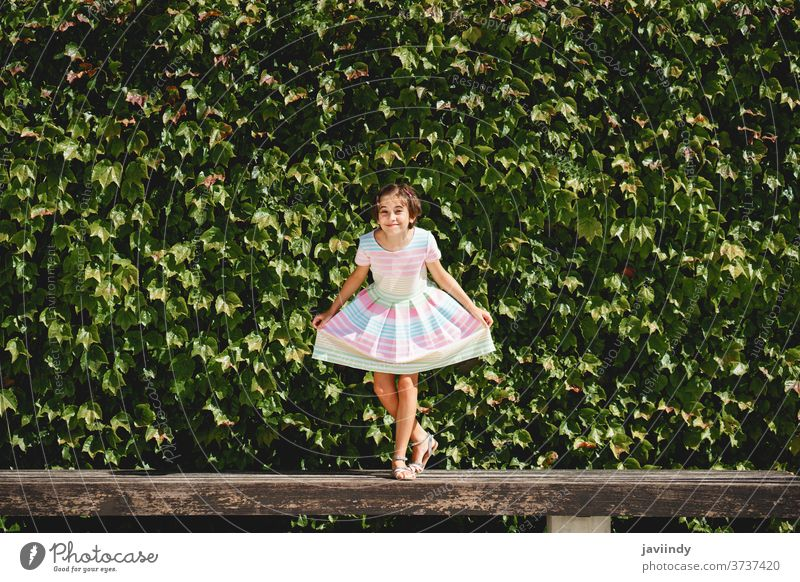 Happy 9-year-old girl in a pretty dress playing kid little child leaves wall urban summer cute city female young style childhood fashion street beautiful