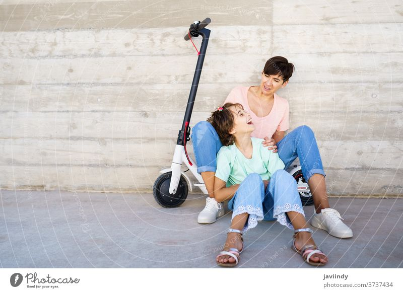 Mother and daughter sitting on an electric scooter mother girl woman eco transportation urban lifestyle modern leisure city ride female young active smile bike