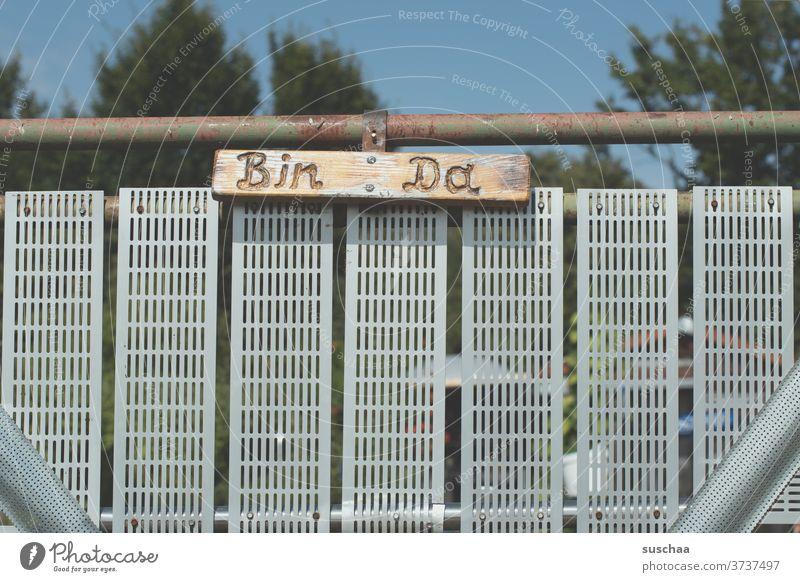 "Garden gate marked ""bin da"" Garden door Goal Communication Iron gate iron rod Metal metal grid Inscription Letters (alphabet) words I'm here. Clue Entrance"