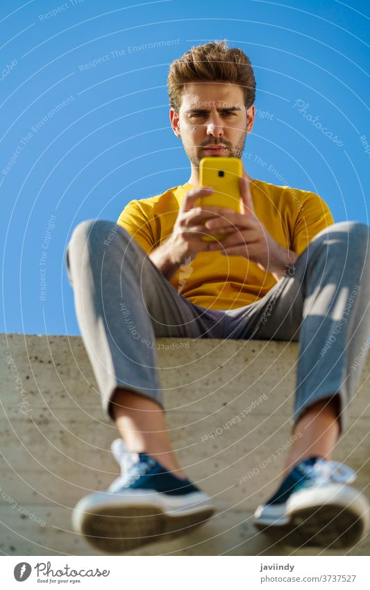Man using his smartphone sitting on a ledge outside man male lifestyle outdoor young guy hairstyle cell background modern casual communication millennial white