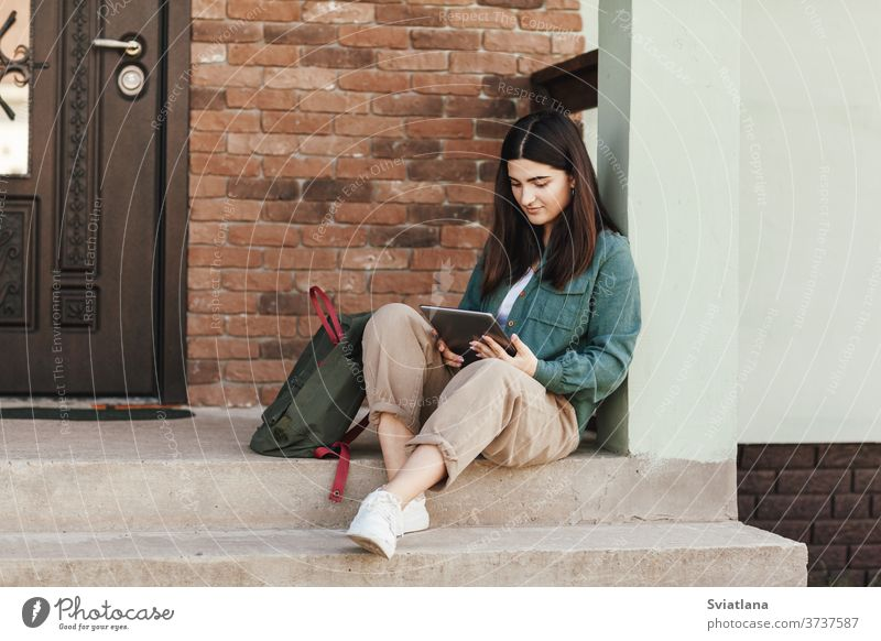 Young female student sitting on steps and studying with tablet in college or private school, technology teaching concept. Technology, education, leisure concept