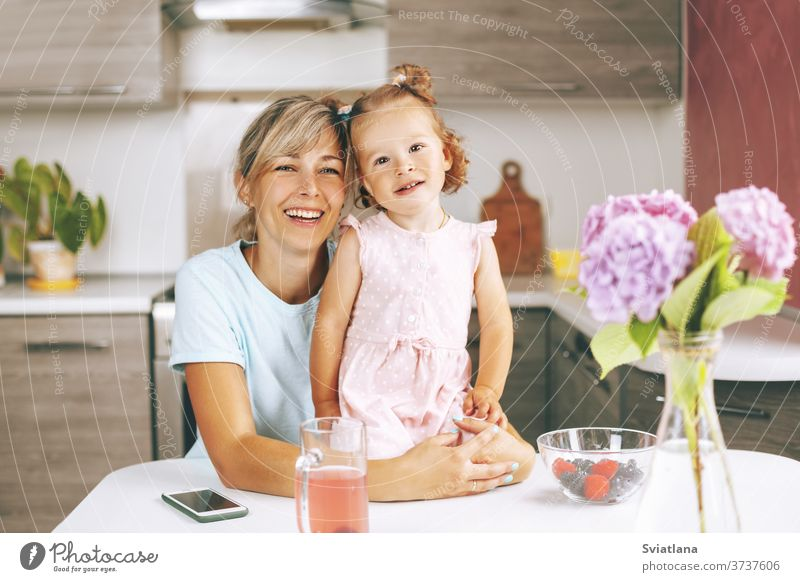 Portrait of an attractive young woman and her little daughter sitting in the kitchen and smiling. On the table is a bouquet of hydrangeas, berries and a glass of juice, side view