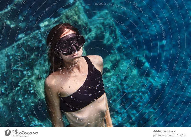 Young woman in diving mask swimming underwater diver goggles snorkel scuba sea ocean young female clean transparent holiday vacation adventure lifestyle