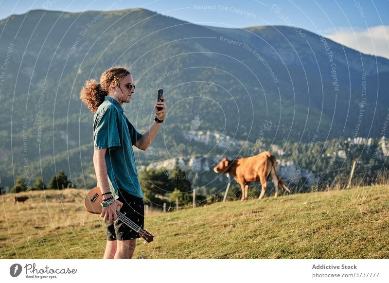 Man taking photo of highland landscape take photo man mountain relax smartphone using memory hipster weekend male scenery ukulele picture amazing hill summer
