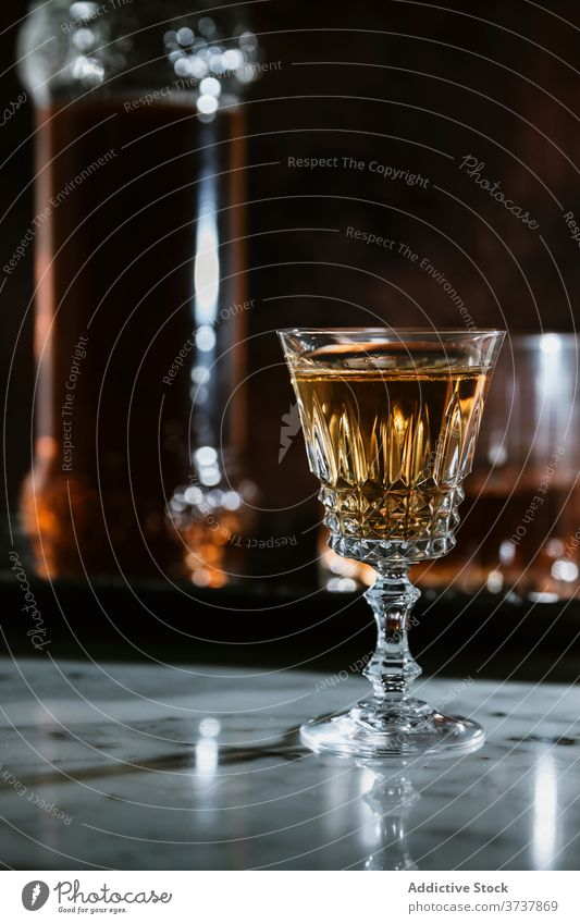 Glass of alcohol beverage on marble table whiskey bar glass drink bottle serve counter booze refreshment pub transparent modern style cold event celebrate