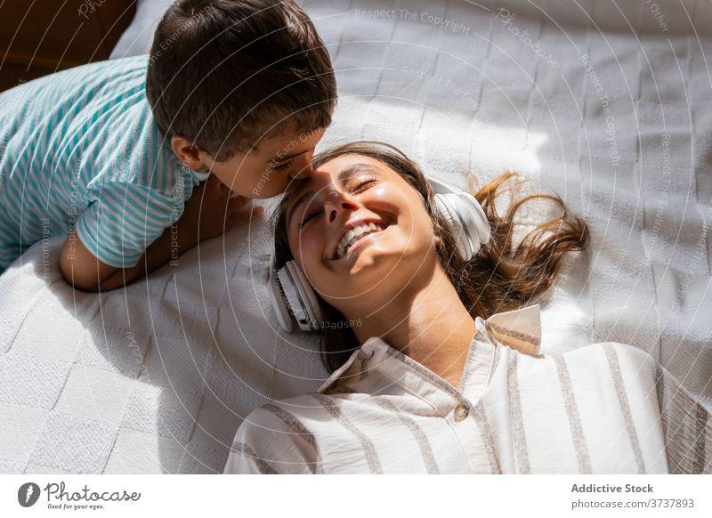 Boy kissing cheerful mother in headphones son listen music happy bed weekend rest love toddler boy child kid woman comfort entertain bedroom lifestyle joy lying