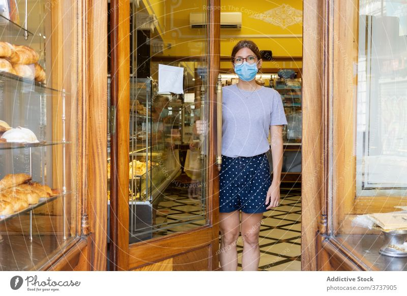 Woman in mask in bakery bakehouse seller woman interior door doorway medical covid female cozy stand new normal safety staff protect profession specialist