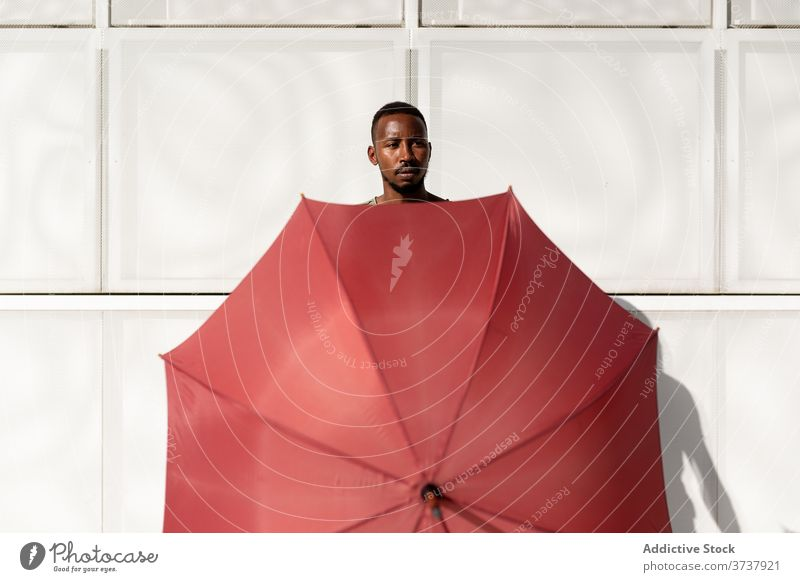 African American man with umbrella in street cover hide summer sunny city urban pavement male ethnic black african american sidewalk body town trendy weather