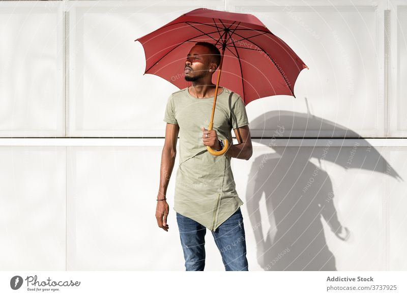 Ethnic man on sunny day on street enjoy summer city umbrella hide relax calm serene urban male ethnic black african american building stand rest handsome trendy