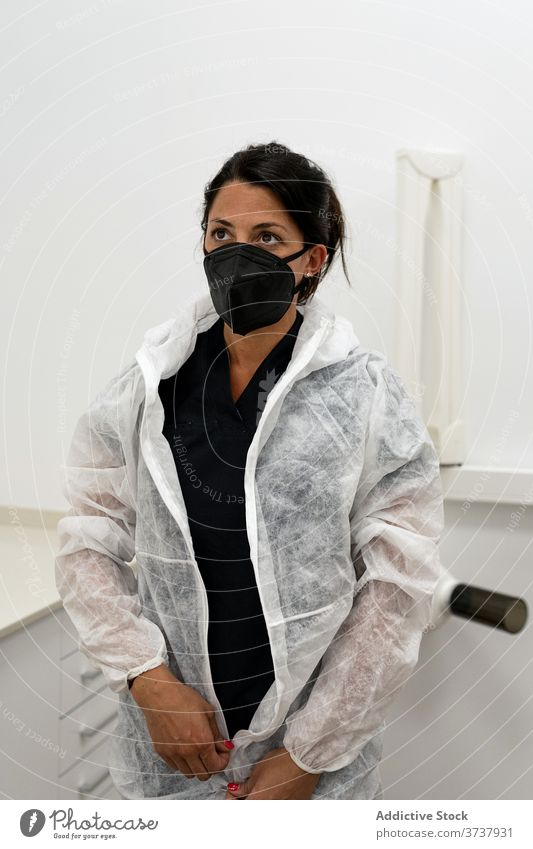 Doctor putting on PPE suit medic coronavirus protect mask put on covid contagious doctor safety ppe woman medicine medical professional wear disease female