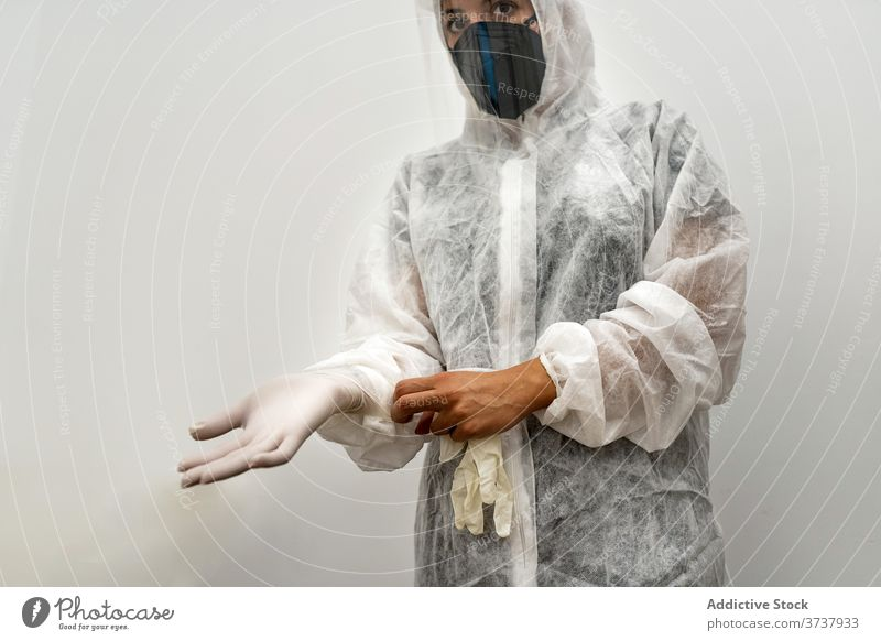 Doctor in PPE suit putting on gloves medic coronavirus protect mask put on covid contagious doctor safety ppe woman medicine medical professional wear disease