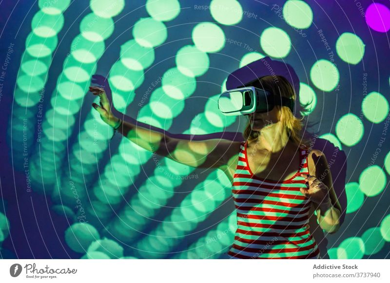 Woman in VR goggles exploring virtual reality woman vr headset touch experience explore illuminate projector technology innovation gadget entertain digital