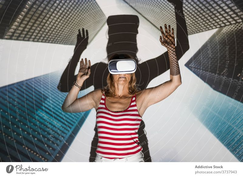 Excited woman in VR headset exploring virtual city vr virtual reality skyscraper building urban goggles touch excited experience effect explore technology