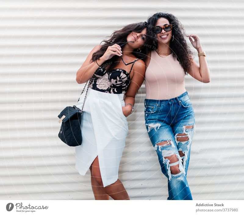 Cheerful young women posing in the street relationship girlfriend happy chill cheerful relax rest together ethnic latin female lifestyle lesbian lgbt bonding