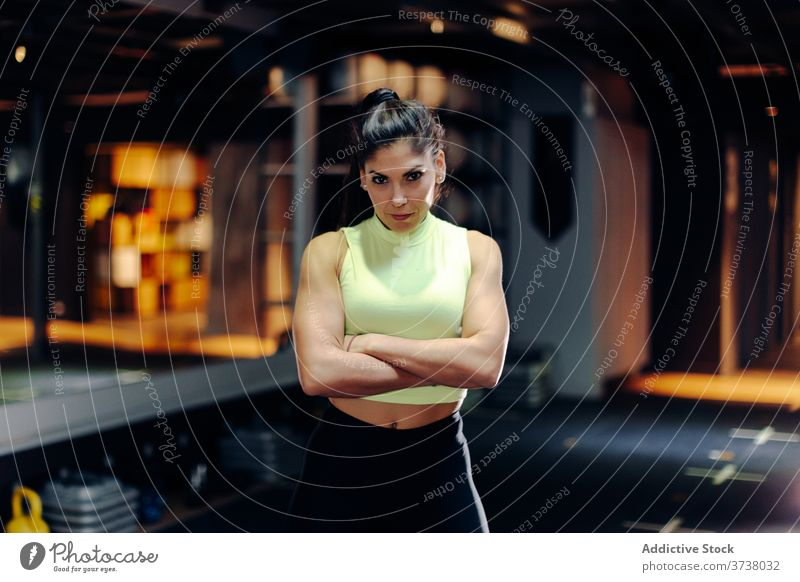 Confident fit woman standing in gym sporty confident determine serious muscular strong athlete sportswoman young female workout training power motivation