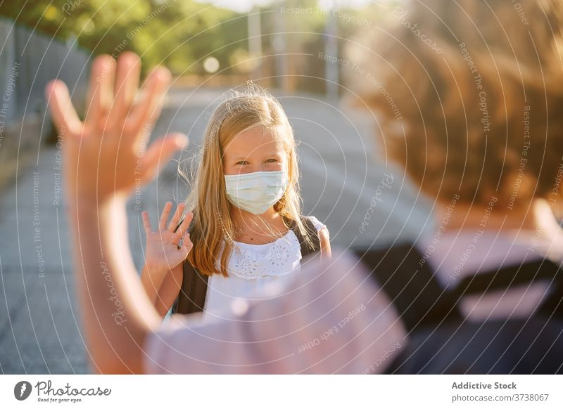 Two kids with a mask greeting with her hand from a distance greetings schoolboy prevent avoid respiratory spread breath pandemic prevention corona epidemic
