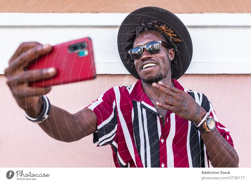 Cheerful ethnic man in stylish outfit taking selfie on street style fashion smartphone cheerful trendy funky hipster young sunglasses stripe modern male