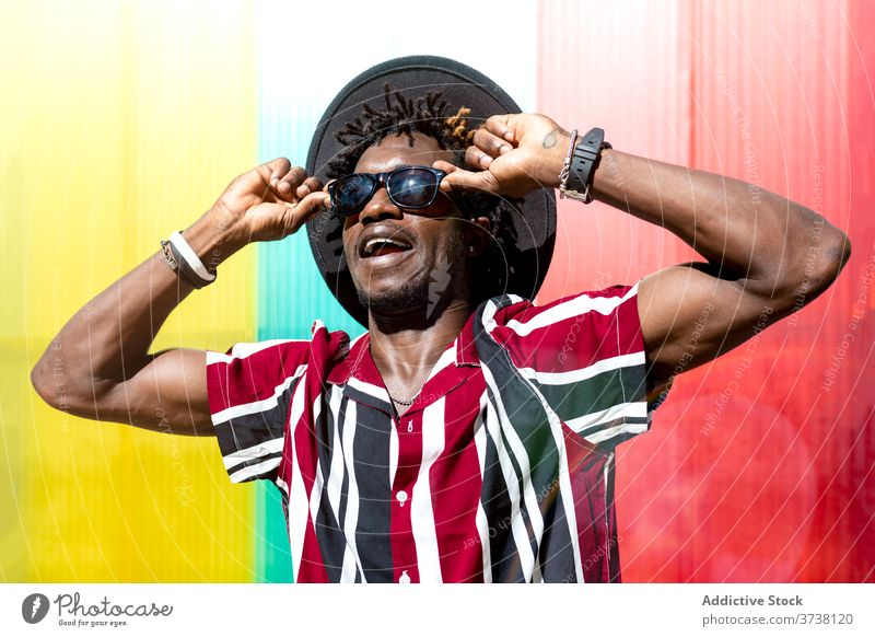 Stylish ethnic man in sunglasses and hat style fashion trendy colorful stripe young modern male african american black hipster multicolored confident accessory