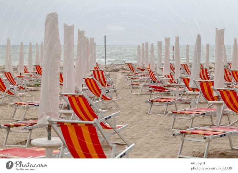 no more summer feeling - folded up deckchairs, parasols and folding chairs on the sandy beach in Italy in front of a sea with waves to the horizon and overcast sky