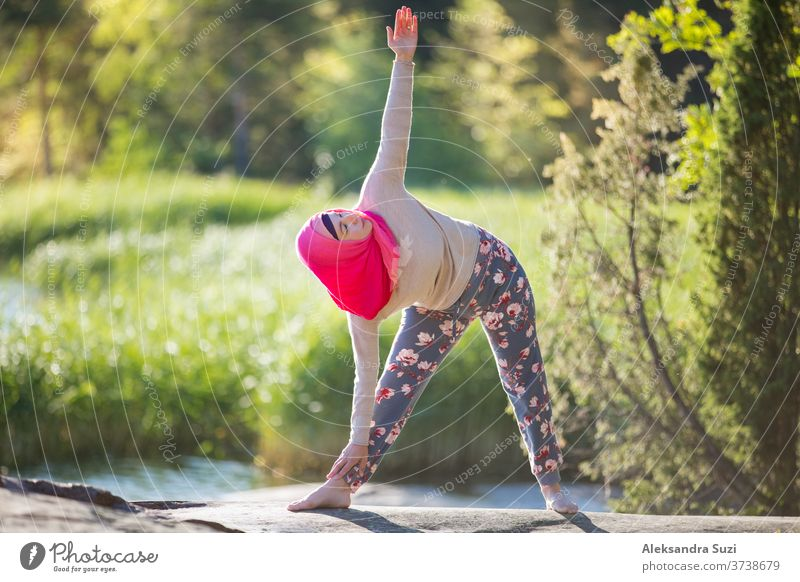 Attractive woman in hijab training in the park, meditating. Doing yoga exercises on fresh air and enjoying early morning. Healthy lifestyle activity adult asana