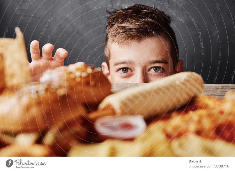 Hungry boy looks at tasty food and take a hamburger from table. Unhealthy food concept fat diet pizza background cholesterol cheeseburger restaurant catering