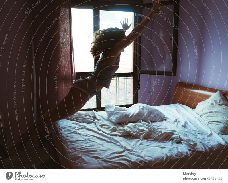 Young charming woman in sleepwear jumping on bed while laughing happily in comfortable bedroom home relax hotel indoors adult inside apartment contemporary