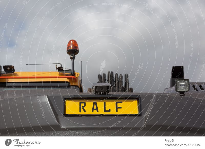 the construction vehicle is called Ralf Construction site Construction site vehicle Name Name plate lamps Rotating beacon Plastic plastic cloudy weather Sky